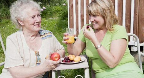 Older person and younger person eating fruit outside