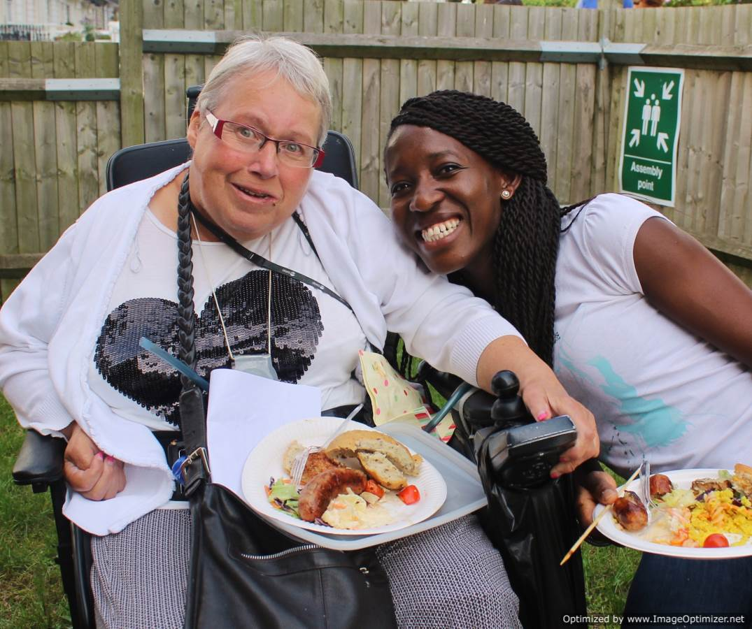 Two women eating food at GIG meeting in a garden.